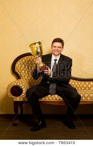 Empresario sonriente con ganar copa en mano en juego sentado en el sofá