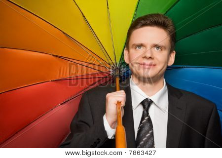 Smiling Businessman In Suit With Multi-coloured Umbrella
