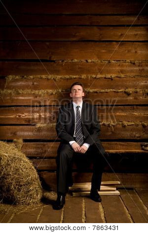 Lonely Businessman Sitting On Bench Near Haystack