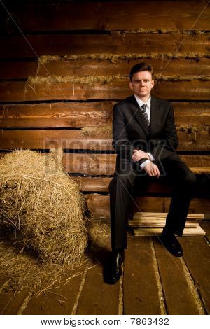 Businessman Sitting On Bench Near Haystack In Wooden Log Hut