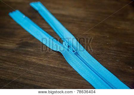 Blue zipper on dark wood background