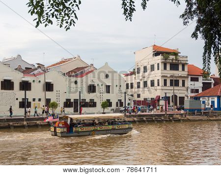A Cruise Full Of Passenger Crossing By The Malacca River.