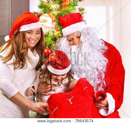 Portrait of happy parent congratulate little daughter with New Year holidays, Santa Claus with big red gift bag, wintertime concept