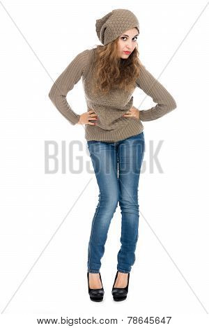 Girl In Full Growth In A Beige Sweater And Jeans.