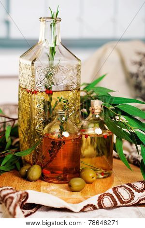 olive oil with rosemary and spices leaves, green olives still life