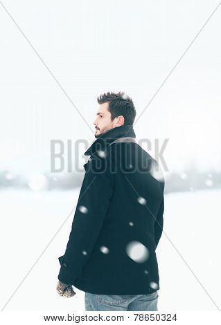 Handsome Man Outdoors Standing In The Winter Blizzard Looks Into The Distance
