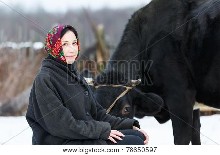 woman in a headscarf near the cow