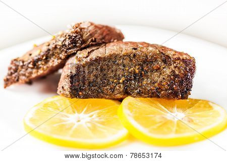 Sliced Roasted Meat With Slices Of Lemon