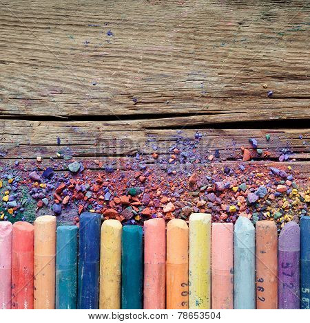 Artistic Pastel Crayons And Pigment Dust On Rustic Wooden Background.