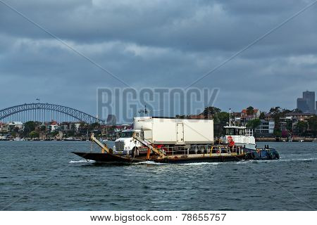 Truck on barge pushed by tug boat