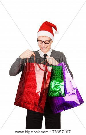 happy young attractive man wearing Santa hat holding shopping bags in Christmas sales