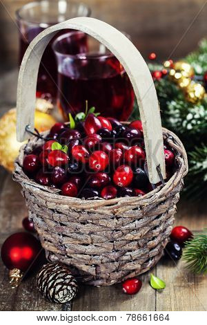 Fresh red cranberries in a basket with juice, spices and pine branches