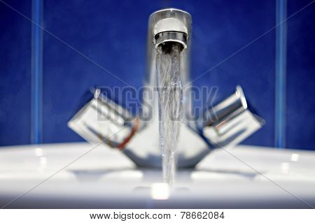 Bathroom faucet. Water flow from chromed steel faucet front view.