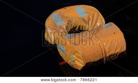 used orange life vest in the water
