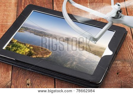 drone aerial photography concept - reviewing aerial pictures of a foggy lake on a digital tablet with a drone rotor, screen picture created by the photographer
