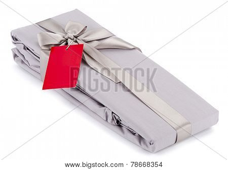 Gift packed cloth wrapped with shiny satin ribbon and red price tag isolated on white background.