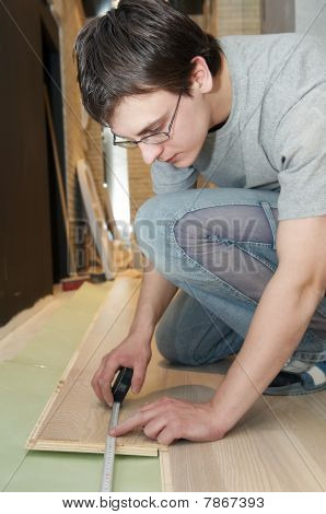 Worker Measuring At Flooring Works