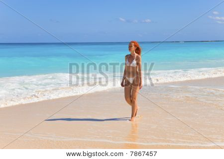 Young graceful woman goes on Oceanside