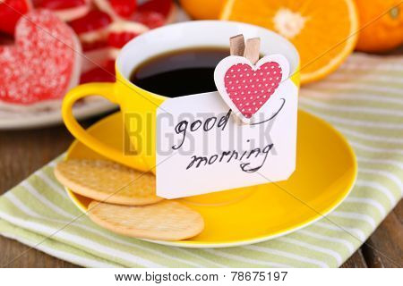 Cup of tea with card that says good morning on table close-up