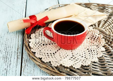 Cup of coffee with lace doily and roll paper on wicker stand, on color wooden background
