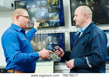 security executive chief discussing activity with worker in front of video monitoring surveillance security system
