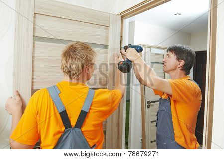 Two male workers carpenters at internal door installation
