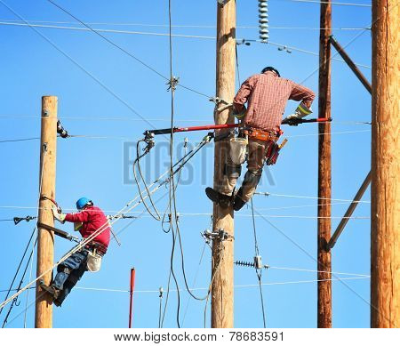two electrical linemen working on lines