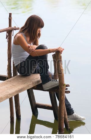 Sad lonely teenage girl sitting on the small wooden dock on the river