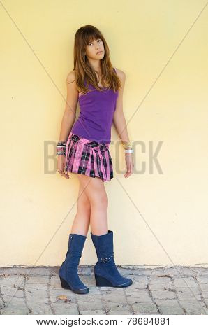 Beautiful teenage girl in short skirt and boots standing beside yellow wall