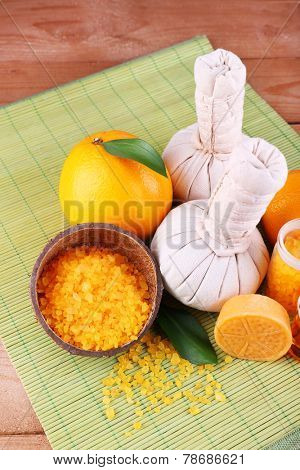 Spa still life with compress balls and coconut shells on color bamboo mat and wooden background