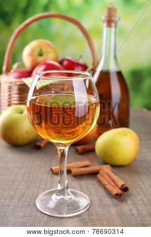 Apple cider in wine glass and bottle, with cinnamon sticks and fresh apples on wooden table, on bright background