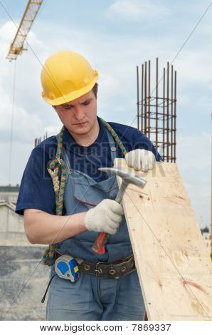 Builder Working With Hammer And Plywood