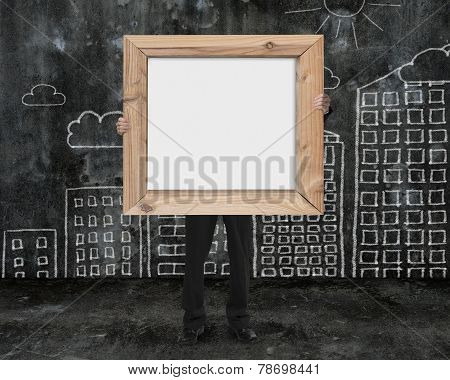Businessman Holding Wooden Frame Blank Whiteboard With Buildings Doodles Wall