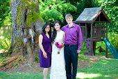 stock photo of biracial  - Beautiful biracial bride standing with her parents - JPG