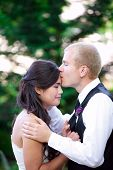 image of biracial  - Caucasian groom lovingly kissing his biracial bride on cheek - JPG