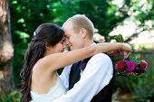 stock photo of biracial  - Caucasian groom holding his biracial bride smiling - JPG