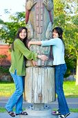 picture of biracial  - Two young biracial teen girls in park hugging a totem pole on sunny day - JPG