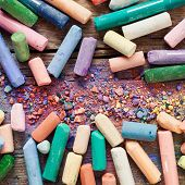 foto of pigment  - Collection of rainbow colored artistic pastel crayons with pigment dust on old wooden desk - JPG