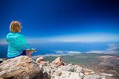 stock photo of fitness  - Young woman doing yoga meditation outside natural beautiful inspirational environment fitness and exercising motivation and inspiration in sunny mountains over blue sky and ocean sea - JPG