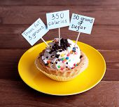 stock photo of dessert plate  - Delicious cake with calories count labels on color plate on wooden table background - JPG
