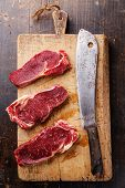 stock photo of ribeye steak  - Raw fresh meat Ribeye steak entrecote and meat cleaver on cutting board on wooden background - JPG
