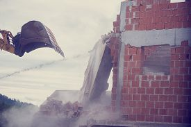 stock photo of backhoe  - Retro image of bucket of a backhoe or mechanical digger demolishing the wall of a brick building with flying masonry and debris - JPG