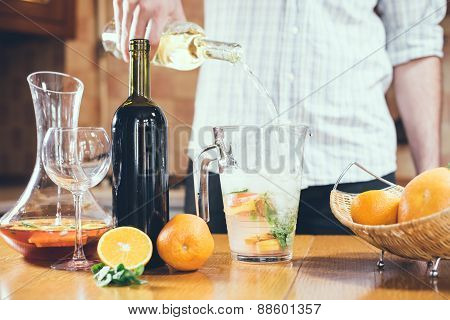 Man pouring white wine into a jar