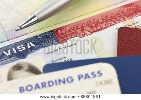 USA Visa, passports, boarding pass and pen - foreign travel background