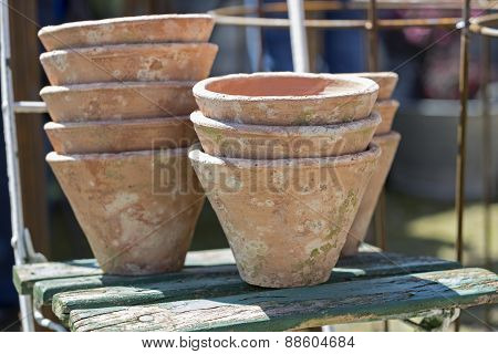 Used clay pots on an old chair