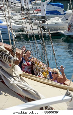 Two Women Among Ropes Of Pleasure Yacht In Summer Sunlight.