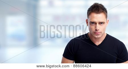 Handsome young man portrait over blue abstract background.