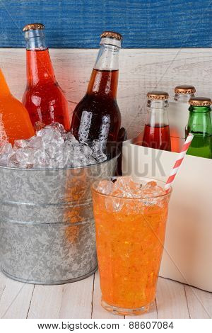 An ice bucket full of soda bottles, a six pack carrier, and a glass of orange soda with straw. Closeup on a rustic set of white washed wood and one blue board.