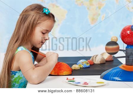 Painting the sun - elementary schoolgirl in science class learning about the solar system
