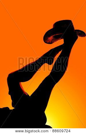 Silhouette Of Womans Legs With Cowboy Hat On Foot Other Foot On Ankle
